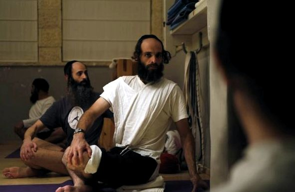 Yoga instructor Avraham Kolberg sits beside a student during a yoga class in Ramat Beit Shemesh