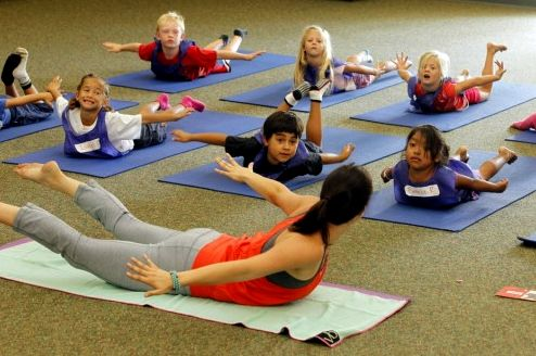 Yoga teacher Jackie Bergeron works with students at Paul Ecke Central Elementary School last week in Encinitas. Students attend two 40-minute yoga classes each week. Eduardo Contreras • U-T